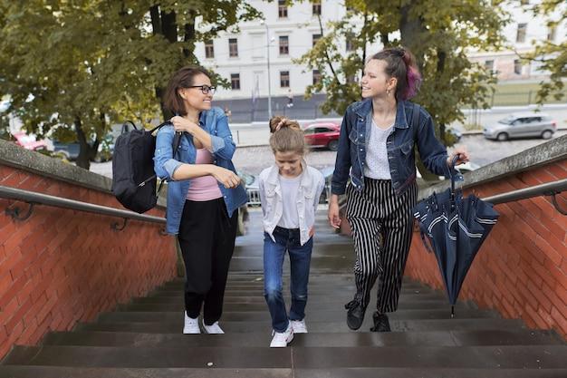 Madre e figli due figlie che camminano sulle scale