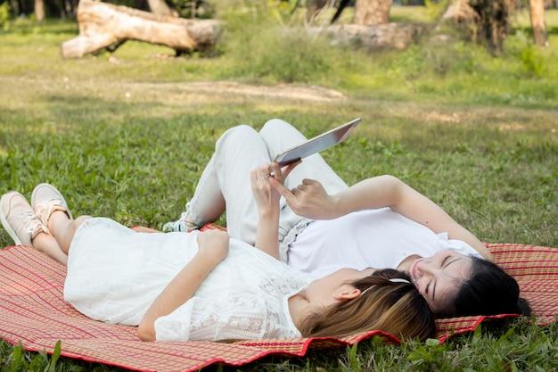 Madre e figli giocano sul tablet sul tappetino.