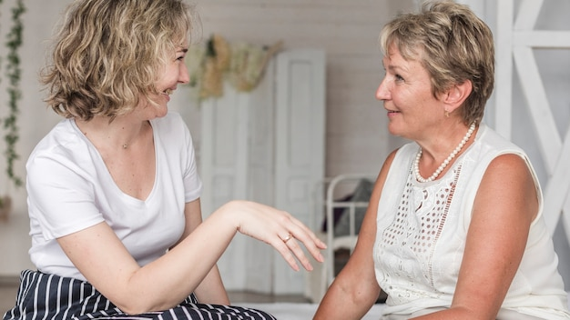 Madre e figlia a parlare a vicenda mentre seduto sul divano
