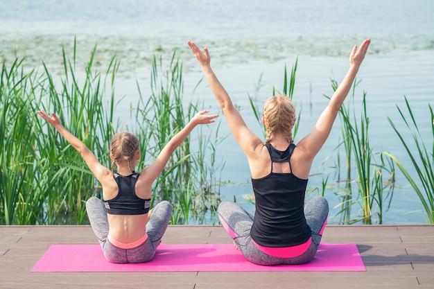 Madre e figlia a praticare yoga su un molo
