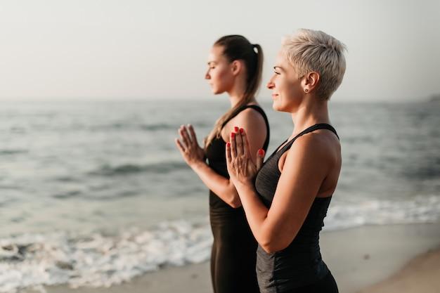 Madre e figlia adatte che meditano e che pregano sull'oceano di mattina