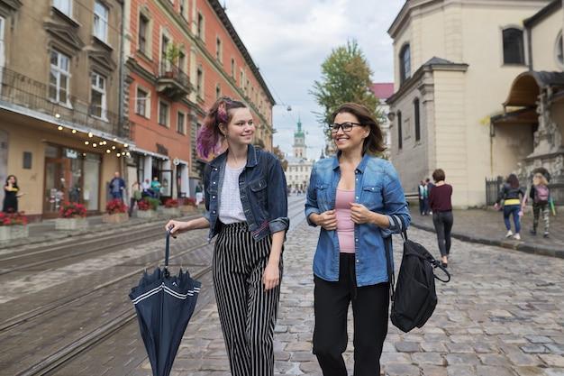 Madre e figlia adolescente che camminano sulla strada della città