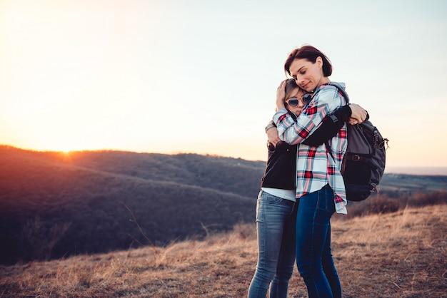 Madre e figlia affettuose che abbracciano su un picco di montagna