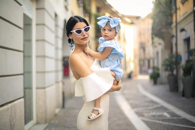 Madre e figlia alla moda che camminano nella via
