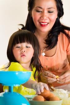 Madre e figlia asiatiche a casa in cucina
