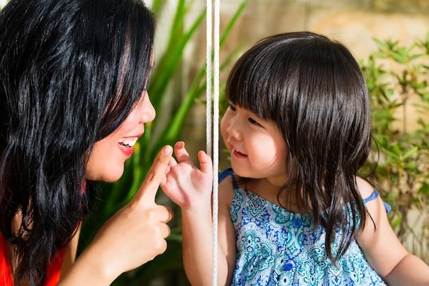 Madre e figlia asiatiche a casa in giardino