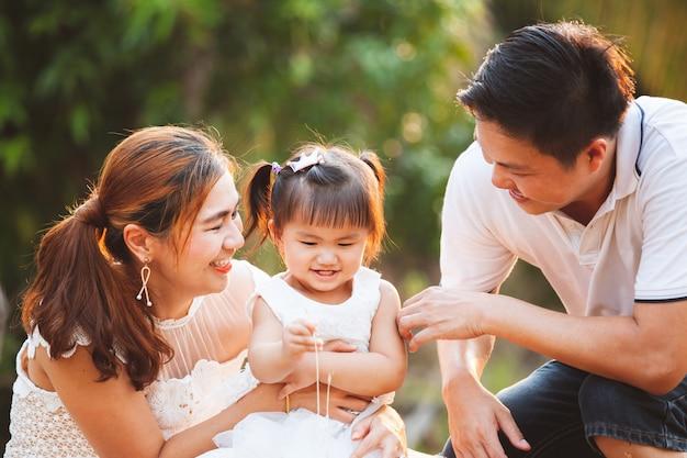 Madre e figlia asiatiche del padre della famiglia che giocano insieme nel parco con amore e felicità