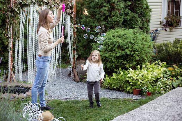 Madre e figlia carina giocando in giardino e soffiando bolle