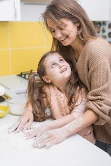 Madre e figlia carina mettendo la farina sul tavolo