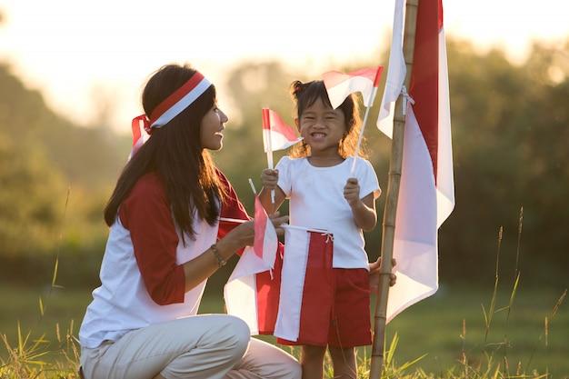 Madre e figlia che alzano bandiera dell'indonesia