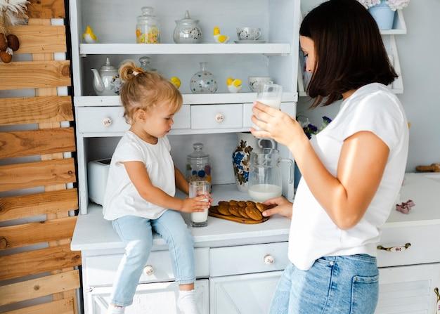 Madre e figlia che bevono latte e che mangiano i biscotti