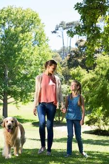 Madre e figlia che camminano nel parco con il cane