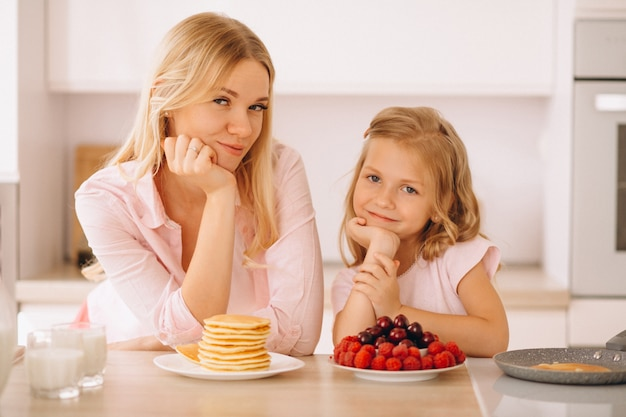 Madre e figlia che cuociono i pancake