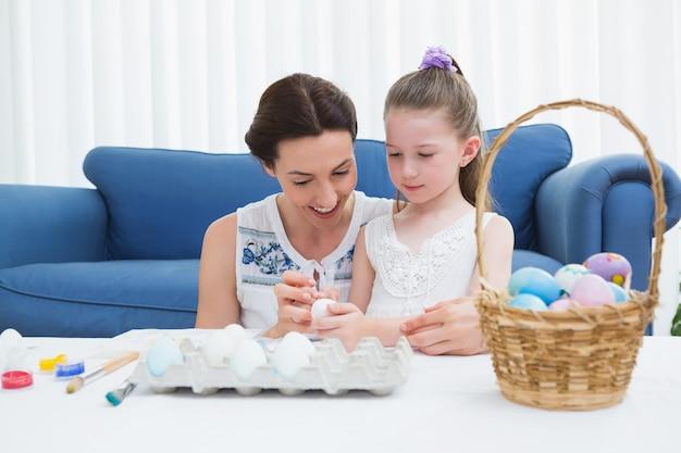 Madre e figlia che dipingono le uova di pasqua