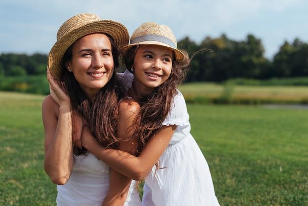 Madre e figlia che distolgono lo sguardo in natura