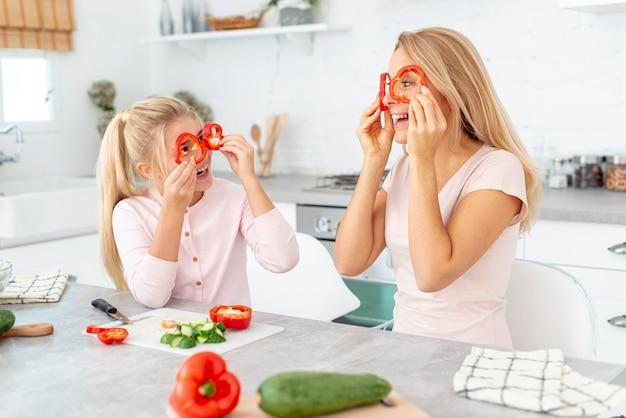 Madre e figlia che fanno i fronti divertenti con i peperoni