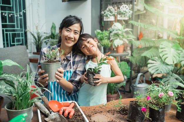 Madre e figlia che fanno il giardinaggio e che piantano alcune piante