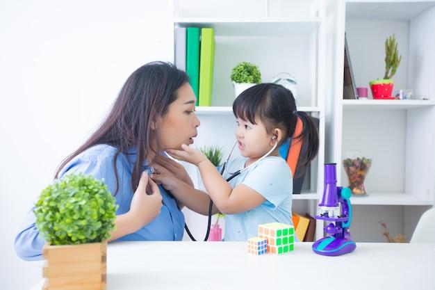 Madre e figlia che giocano al dottore con lo stetoscopio