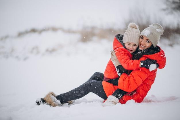 Madre e figlia che giocano nel parco di inverno