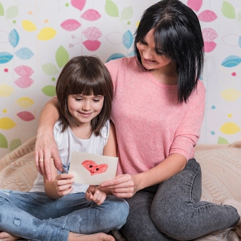 Madre e figlia che leggono la cartolina d'auguri sul letto