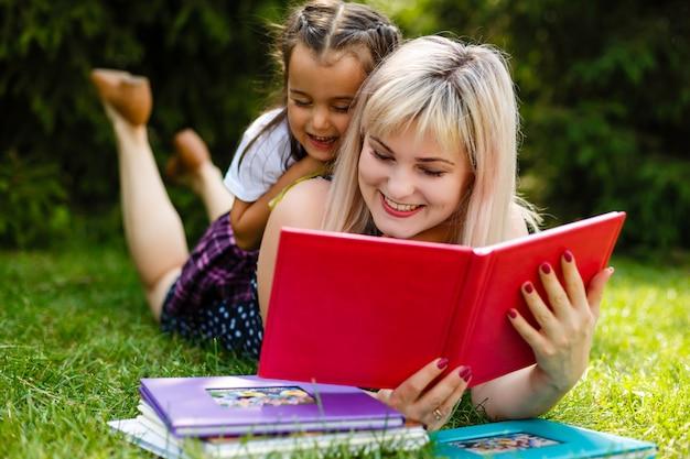Madre e figlia che leggono un libro al parco.