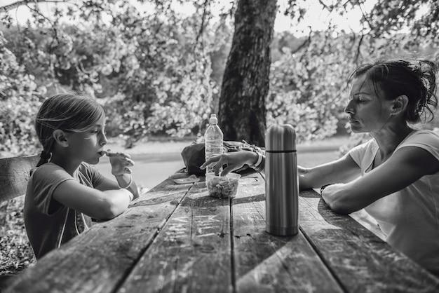 Madre e figlia che mangiano ad un tavolo da picnic