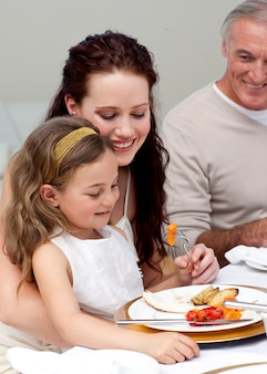 Madre e figlia che mangiano con la loro famiglia