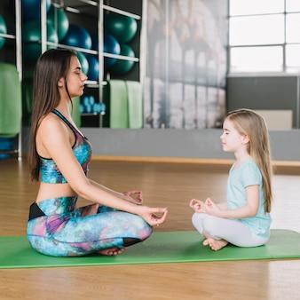 Madre e figlia che meditano insieme sulla stuoia di yoga sul pavimento di legno