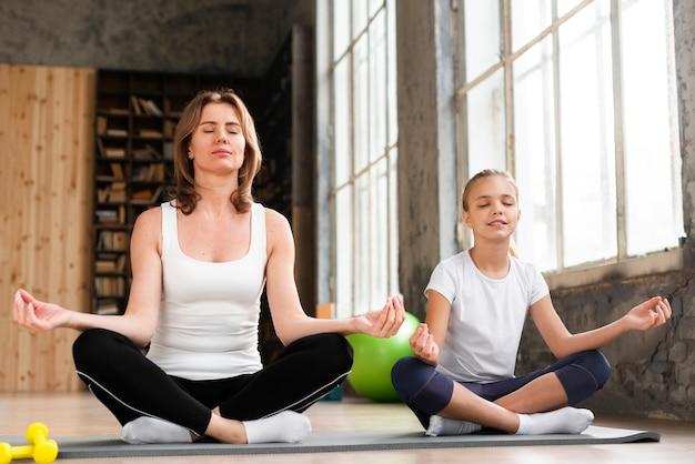 Madre e figlia che meditano su stuoia di yoga