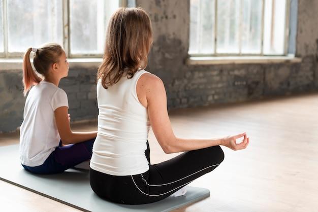 Madre e figlia che meditano su stuoie in palestra