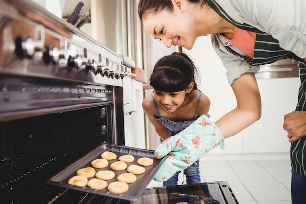 Madre e figlia che mettono i biscotti in forno