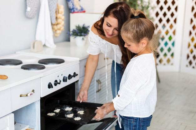 Madre e figlia che mettono il vassoio dei biscotti in forno