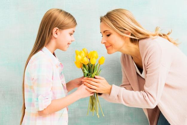 Madre e figlia che odorano il mazzo di fiori