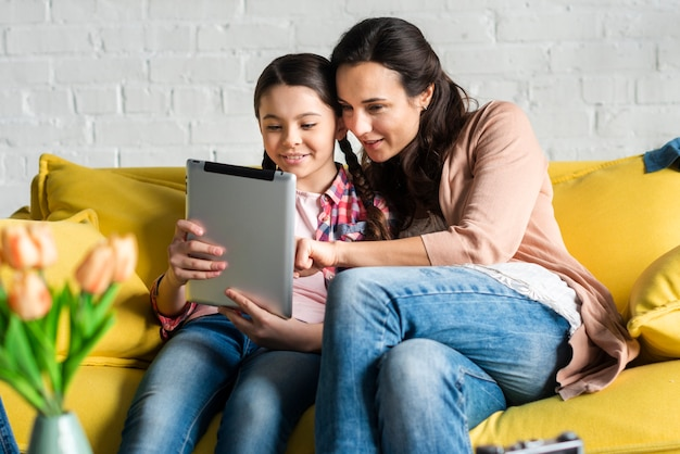 Madre e figlia che osservano su un ridurre in pani digitale