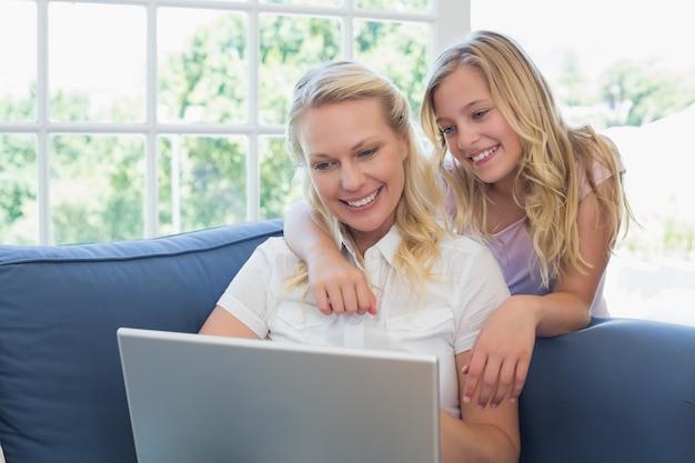 Madre e figlia che per mezzo del computer portatile sul sofà