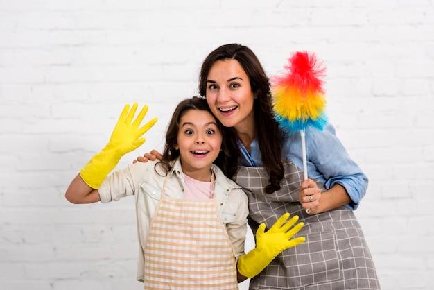 Madre e figlia che posano con gli oggetti di pulizia