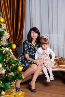 Madre e figlia che posano con l'albero di natale
