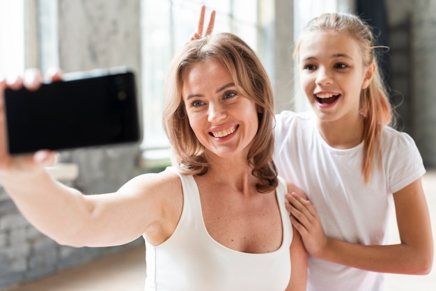 Madre e figlia che prendono selfie divertente