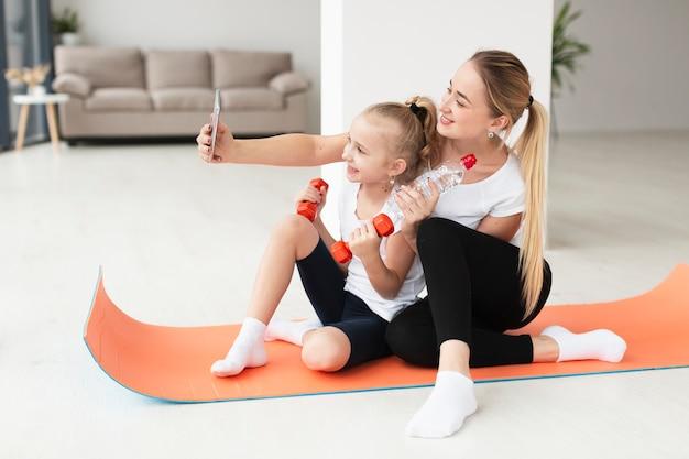 Madre e figlia che prendono selfie mentre tenendo pesi