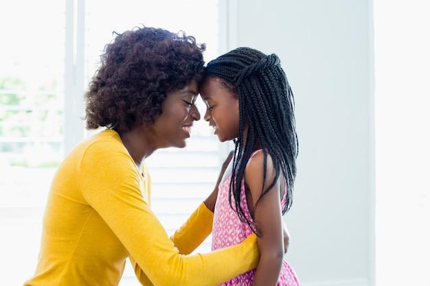 Madre e figlia che si abbracciano faccia a faccia