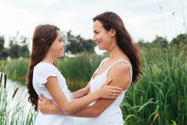Madre e figlia che si abbracciano sul lago