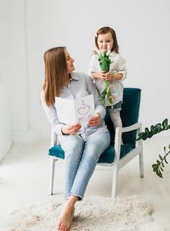 Madre e figlia che si siedono con la cartolina d'auguri