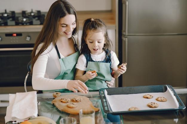 Madre e figlia che si siedono in una cucina con i biscotti