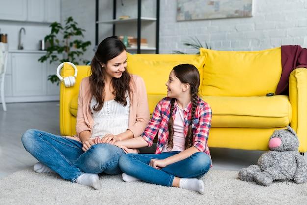 Madre e figlia che si siedono sul pavimento