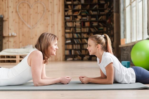 Madre e figlia che si siedono sulla stuoia che se lo esamina