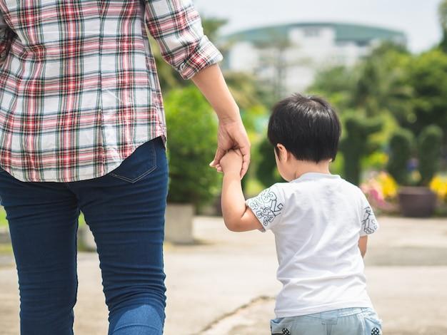 Madre e figlia che si tengono per mano che camminano nel parco. concetto di famiglia di bambino e mamma.