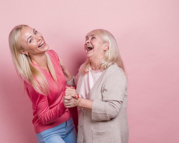 Madre e figlia che si tengono per mano e che scherzano