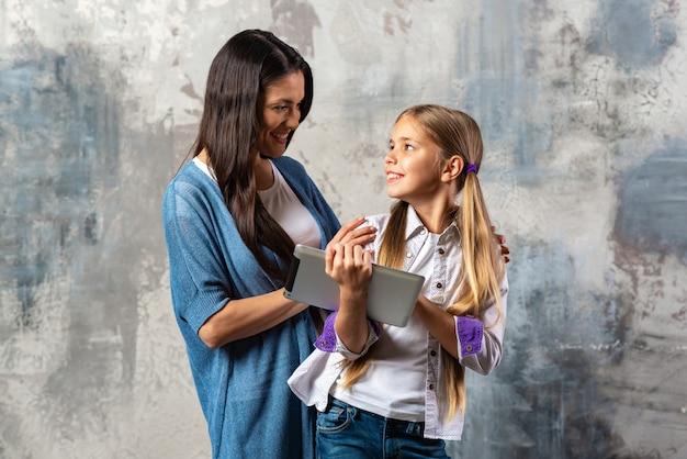 Madre e figlia che tengono lo schermo in bianco della compressa digitale