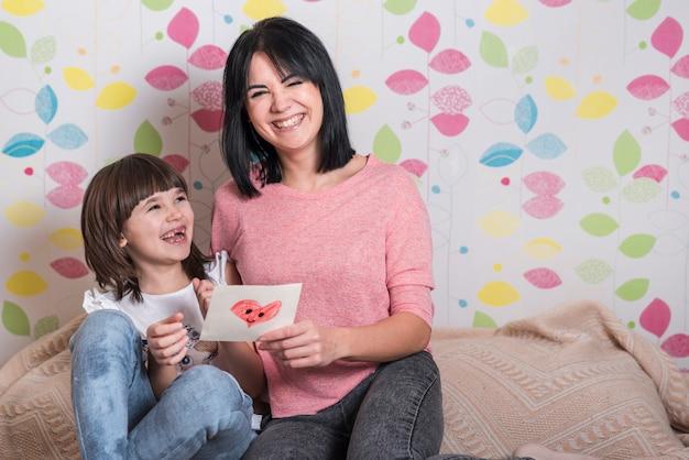 Madre e figlia con biglietto di auguri ridendo