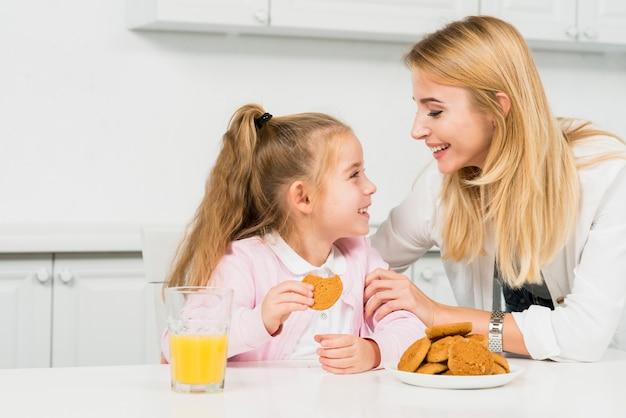 Madre e figlia con biscotti e succo